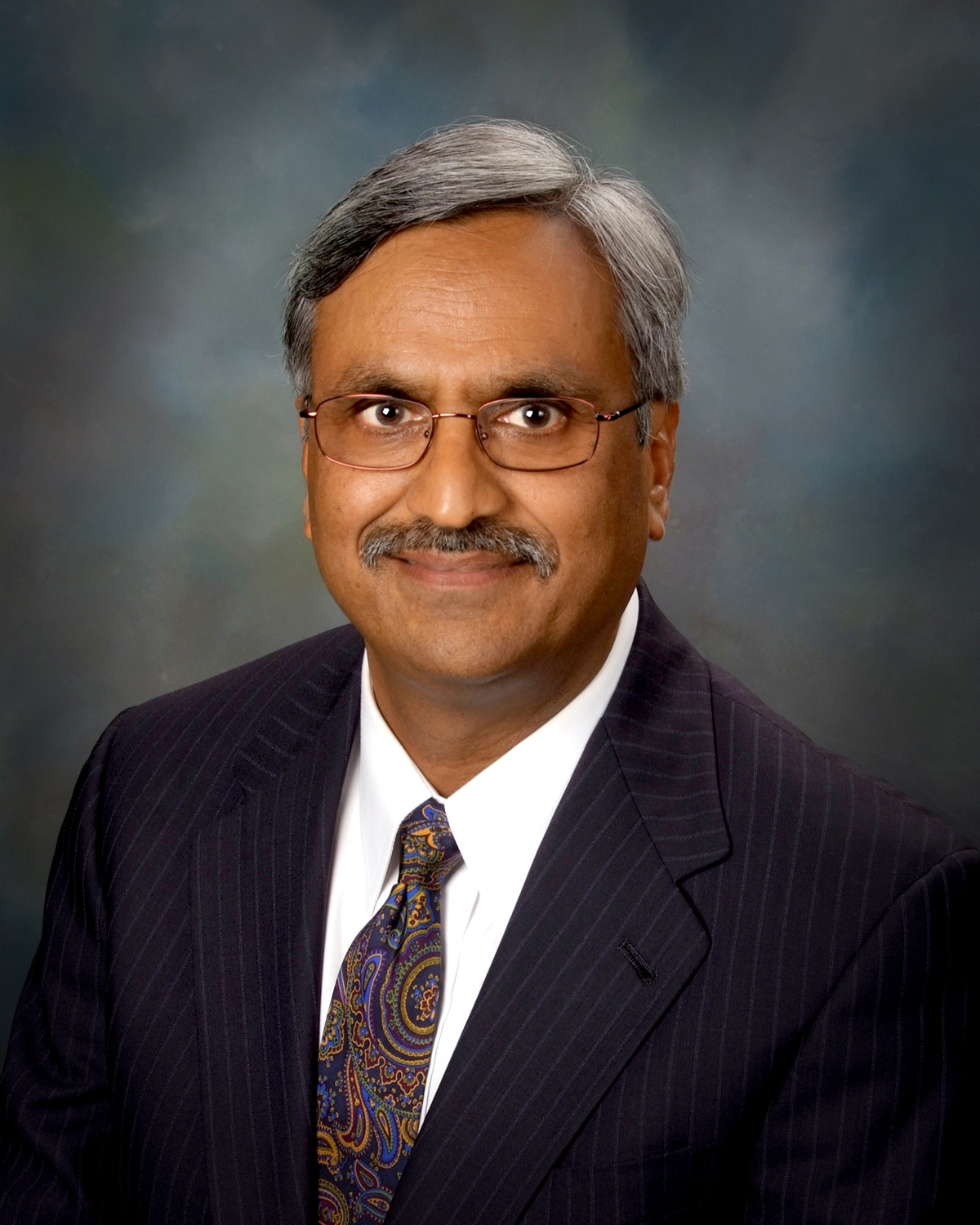 Rakesh Mohan in suit and tie smiling at the camera