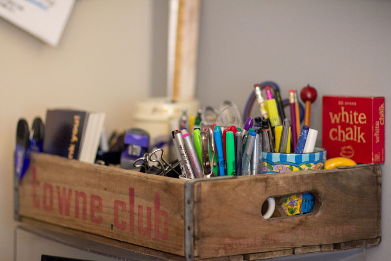 Crate filled with Sheila's school supplies like pens and chalk
