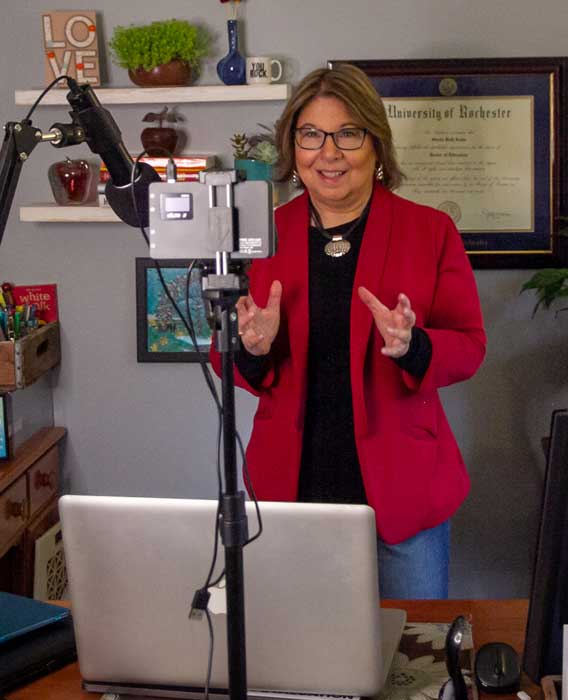 Sheila in coral blazer presenting on camera standing up behind her desk