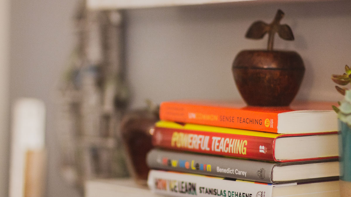Books stacked neatly on a shelf with a metal apple on top